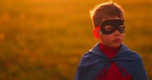 Le garçon dans le masque et le cap d'un superhéros au coucher du soleil dans un domaine clips vidéos
