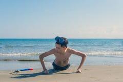 Le garçon dans le masque et le tube naviguants au schnorchel extorqués sur le sable sur la plage sur le fond de mer Le concept de photos stock