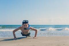 Le garçon dans le masque et le tube naviguants au schnorchel extorqués sur le sable sur la plage sur le fond de mer Le concept de photographie stock libre de droits