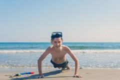 Le garçon dans le masque et le tube naviguants au schnorchel extorqués sur le sable sur la plage sur le fond de mer Le concept de photo libre de droits