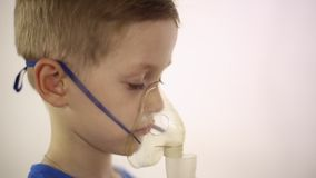 Le garçon dans le masque l'inhalateur est traité banque de vidéos