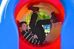 Le garçon dans le pull molletonné noir et blanc joue dans le terrain de jeu dedans Photo stock