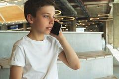 Le garçon dans le T-shirt blanc s'assied à l'intérieur et parle à son téléphone portable Un adolescent utilise un téléphone porta photos stock