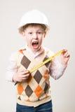 Le garçon dans un casque avec un ruban métrique et crie avec émotion Images stock