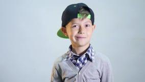 Le garçon dans un chapeau clignote un oeil banque de vidéos