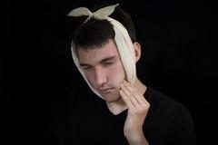 Le garçon dans un foulard est souffrance du mal de dents douloureux Photos stock