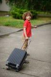 Le garçon de 8-9 ans traîne une grande valise sur des roulettes Image libre de droits
