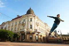 Le garçon de danse fait des pirouettes sur les rues de ville de matin Image libre de droits