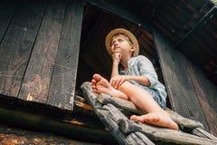 Le garçon de Dreming s'assied sur le chef de grange Images stock