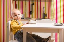 Le garçon de famille de bébé s'asseyent sur la cuisine de jouet Photos stock