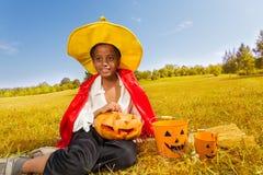 Le garçon de Halloween s'assied sur l'herbe jaune avec le potiron Photos libres de droits