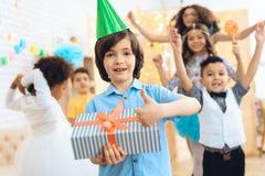 Le garçon de joyeux anniversaire dans le chapeau de fête vert prouve qu'il est heureux avec le cadeau Photographie stock