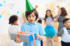 Le garçon de joyeux anniversaire dans le chapeau de fête vert prouve qu'il est heureux avec le cadeau Image stock