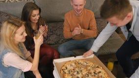 Le garçon de l'adolescence amène à un emporter la pizza savoureuse et les amis gais prenant des tranches de plat Photos stock
