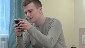 Le garçon de l'adolescence beau utilise smilingly le smartphone dans sa chambre dans la maison d'étudiant Photos libres de droits