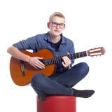 Le garçon de l'adolescence caucasien dans le bleu porte des lunettes et joue le classique Photos libres de droits