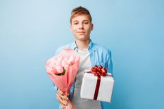 Le garçon de l'adolescence donne un cadeau et les fleurs, un homme dans l'amour, sur un fond bleu photos stock