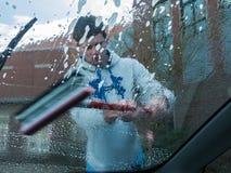 Le garçon de l'adolescence frotte la fenêtre de voiture à l'événement de charité, Orégon Images stock