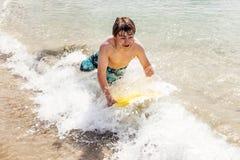 Le garçon de l'adolescence a l'amusement avec son conseil de boogie Image libre de droits