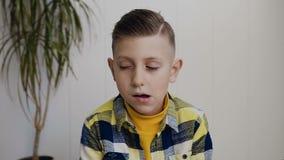 Le garçon de l'adolescence mignon avec des yeux bleus est cligner de l'oeil à l'appareil-photo et au sourire Le petit garçon cauc clips vidéos