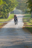 Le garçon de l'adolescence portent la fille de l'adolescence sur la route Images libres de droits