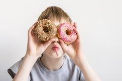 Le garçon de l'adolescence regarde dans des trous de beignet et des grimaces drôles photos libres de droits