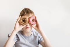 Le garçon de l'adolescence regarde dans des trous de beignet et des grimaces drôles images stock
