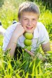 Le garçon de l'adolescence tient les pommes vertes Images stock