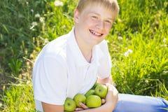 Le garçon de l'adolescence tient les pommes vertes Photo libre de droits