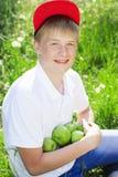 Le garçon de l'adolescence utilise le chapeau rouge tenant des pommes photo libre de droits
