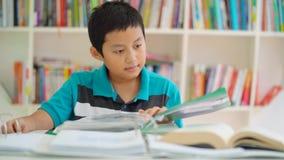 Le garçon de la préadolescence apprend avec des livres dans la bibliothèque banque de vidéos