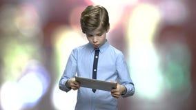 Le garçon de la préadolescence joue sur le comprimé numérique banque de vidéos