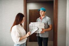 Le garçon de livraison de pizza prend une astuce de client images stock
