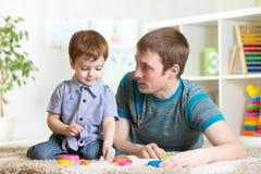 Le garçon de père et d'enfant jouent ensemble d'intérieur à la maison image stock