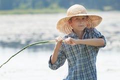 Le garçon de pêcheur à la ligne jette l'amorce de la canne à pêche faite main Photographie stock