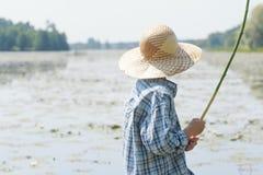 Le garçon de pêcheur à la ligne lie d'amitié la canne à pêche faite main Photographie stock