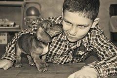 Le garçon de pièce joue avec un petit teckel de chien Image stock