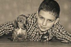 Le garçon de pièce joue avec un petit teckel de chien Photos stock