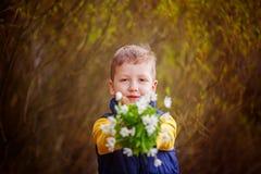 Le garçon de portrait étire un bouquet des fleurs de ressort Images stock