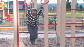 Le garçon de sept ans accroche sur les anneaux gymnastiques sur le terrain de jeu clips vidéos