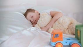 Le garçon de sept ans dormant avec ses jouets soutiennent et voiture en plastique banque de vidéos