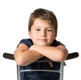 Le garçon de sept ans s'assied à cheval sur une chaise Image stock