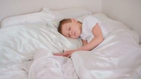 Le garçon de sept ans tombe se coucher endormi dans le lit banque de vidéos