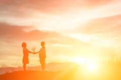 Le garçon de silhouette envoient des fleurs aux filles scène et amour romantiques Co Photographie stock libre de droits