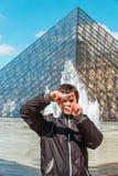 Le garçon de sourire à Paris encadrent faire des gestes devant le pyra de Louvre Images stock