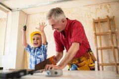 Le garçon de sourire aide à son granfather dans l'atelier Image stock