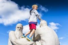 Le garçon de sourire au-dessus de la sculpture dans Vigeland se garent à Oslo, Norvège Photo libre de droits