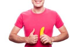 Le garçon de sourire avec la banane montre CORRECT Photos stock