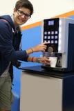 Le garçon de sourire boit du café pendant la coupure photographie stock libre de droits