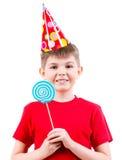 Le garçon de sourire dans la participation rouge de T-shirt a coloré la sucrerie Photos stock